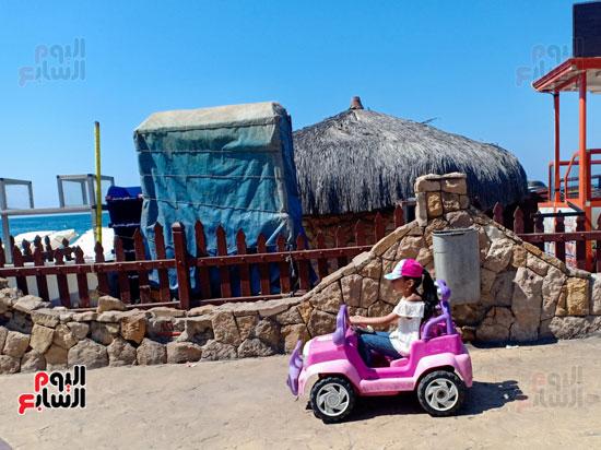 الاطفال يلعبون على الشاطئ بالسيارات
