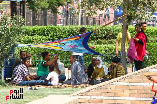 الزوار يحتمون من حرارة الشمس تحت الشجر والملايات