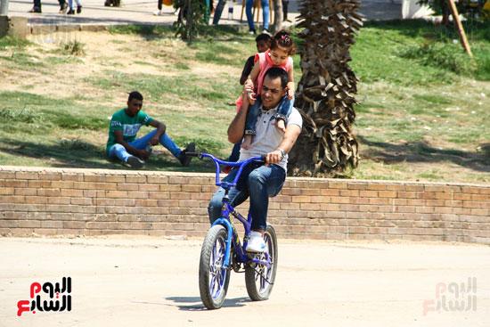 اب يحمل ابنتة على كتفة اثناء ركوب العجلة