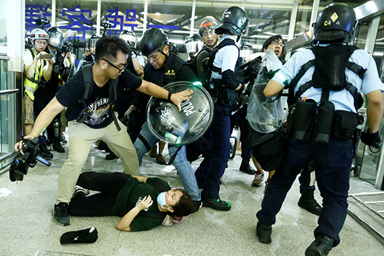 متظاهرة على الأرض وسط هجوم من الشرطة
