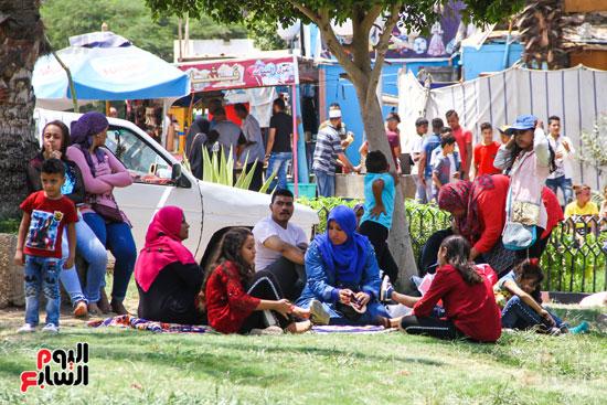 الزوار يحتمون من حرارة الشمس تحت الشجر (3)