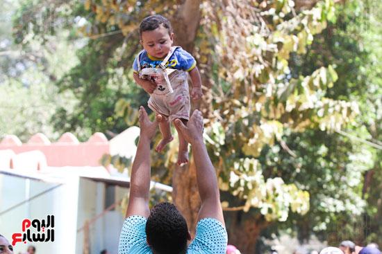 طفل  يلعب مع ابنه بحديقة الحيوان