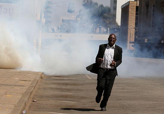 مواطن يفر بعيدا من الغاز المسيل للدموع