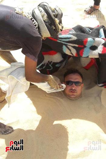 صاحب حمام يمسح وجه طالب للعلاج بعد دفنه بالرمال