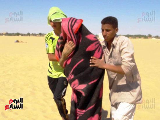 شابين يمسكان برجل بعد خروجه من الرمال لاستكمال خطوات العلاج