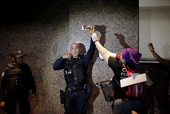 Demonstrators attack a policeman