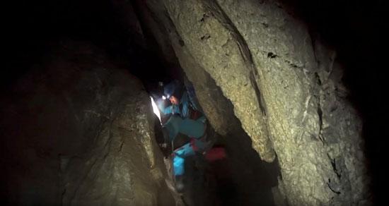 أحد رجال الانقاذ يحاول الدخول للكهف