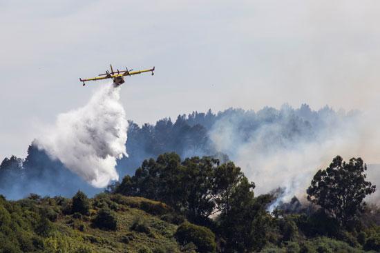 طائرة إطفاء تحلق فوق النيران