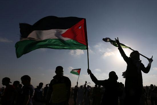 المتظاهرين يرفعون الاعلام الفلسطينية