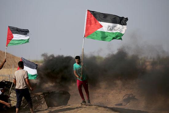 شاب فلسطينى يرفع علم فلسطين