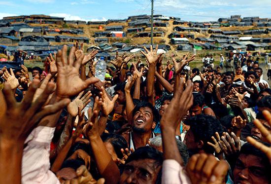 لاجئون الروهينجا يمدون أيديهم لتلقي المساعدات