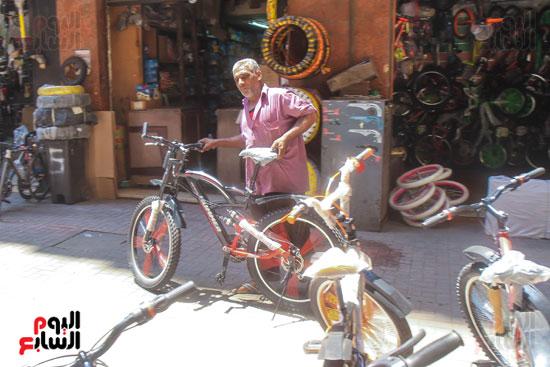 احد الفنيين ينقل الدراجة