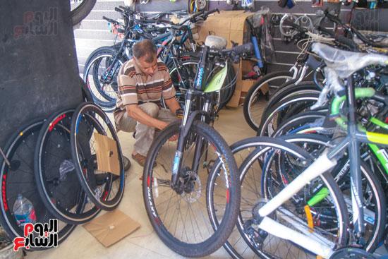 فني يقوم بصيانة الدراجات قبل بيعها