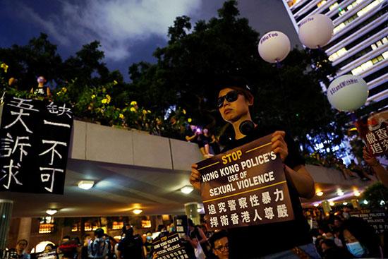 متظاهرة ترفع اللافتات المناهضة