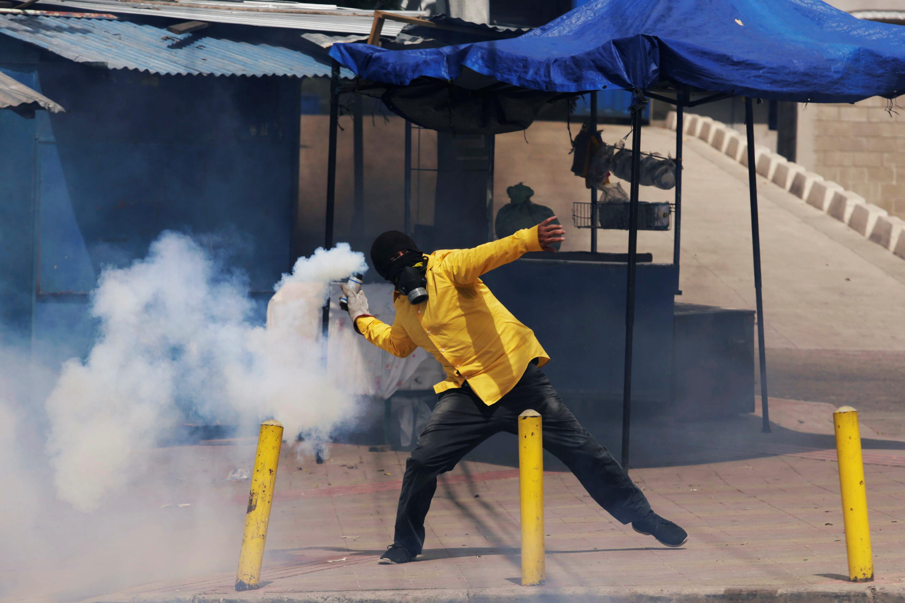 1359466-أحد-المتظاهرين-يلقى-قتبلة-غاز-على-قوات-الامن