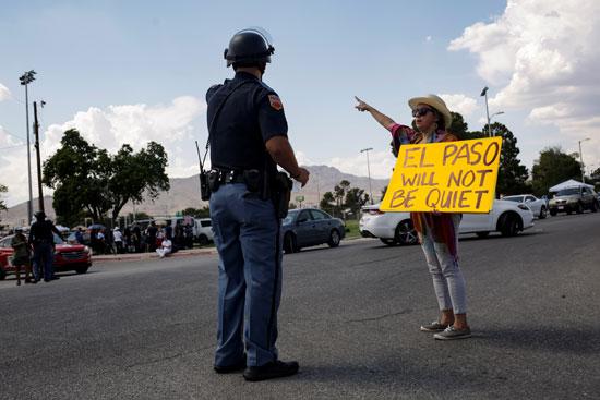 49308-احدى-التظاهرات-تتحدث-مع-رجل-شرطة-امام-مكان-تواجد-ترامب