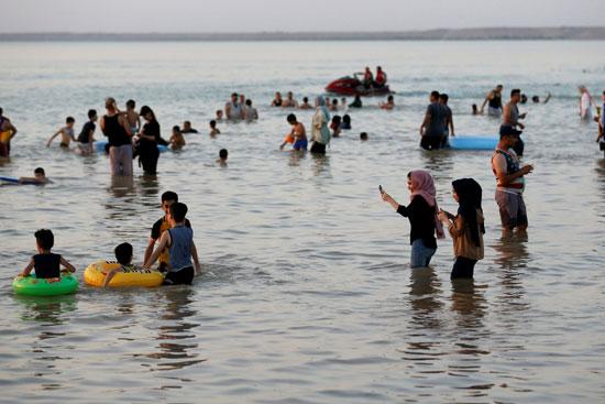 عراقيون يهربون من الحر الشديد بالسباحة فى بحيرة الحبانية (2)