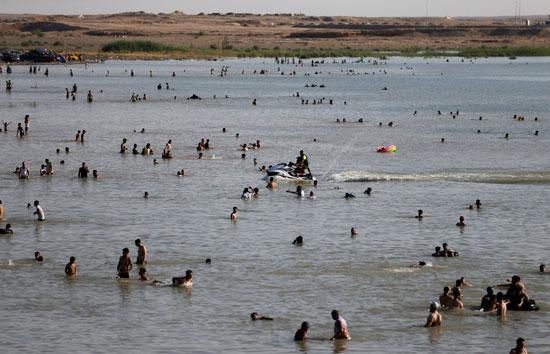 عراقيون يهربون من الحر الشديد بالسباحة فى بحيرة الحبانية (8)