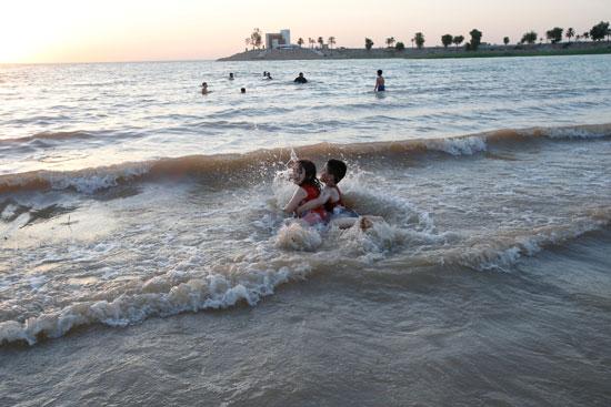 عراقيون يهربون من الحر الشديد بالسباحة فى بحيرة الحبانية (6)