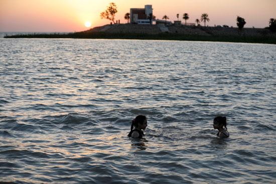 عراقيون يهربون من الحر الشديد بالسباحة فى بحيرة الحبانية (9)