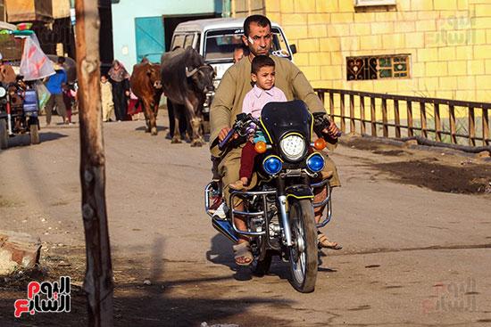 اب يوصل ابنائه للمدرسة علي دراجته النارية