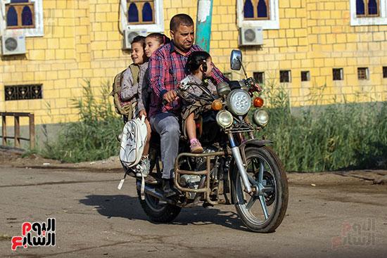 اب يوصل ابنائه للمدرسة علي دراجته النارية (2)