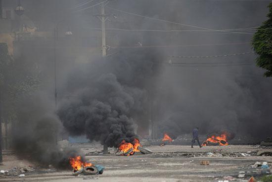 رجل يمشي عبر إطارات محترقة أثناء احتجاج خارج مقر البرلمان
