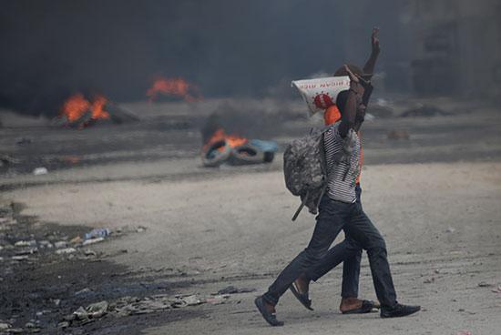 المتظاهرون يرفعون أذرعهم وهم يمشون بجوار الإطارات المحترقة