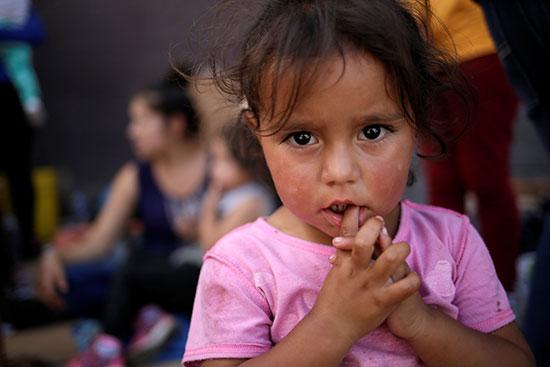 طفلة مكسيسكة تنتظر مع اسرتها العبور للولايات المتحدة