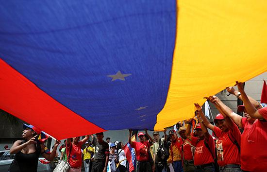 المتظاهرون يحملون علم عملاق لبلادهم