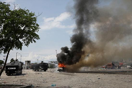 الشرطة الوطنية الهايتية تطفئ حافلة الشرطة المحترقة أثناء المظاهرة
