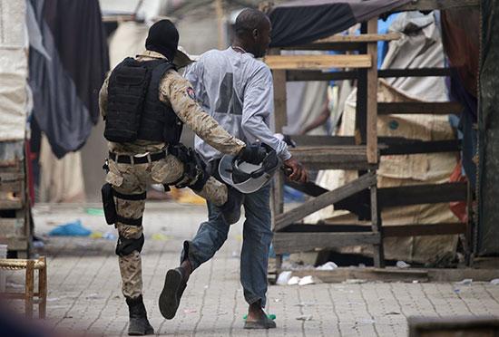ضابط بالشرطة الوطنية الهايتية يركل رجلاً أثناء احتجاج
