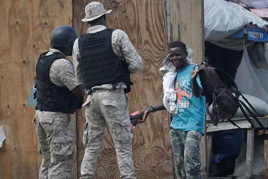 صبي يعرض محتويات حقيبته أمام ضباط الشرطة الوطنية الهايتية