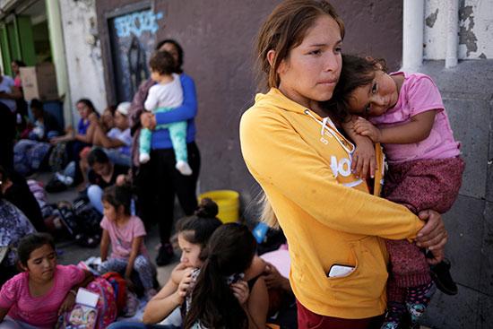 امراة مكسيكسة تحمل طفلها عند جسر عبور الحدود لأمريكا