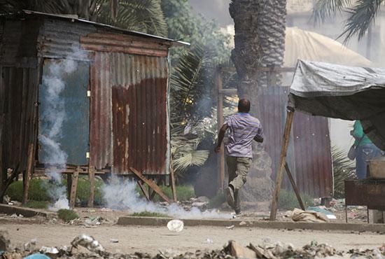 رجل يهرب من الغاز المسيل للدموع أثناء احتجاج خارج مقر البرلمان