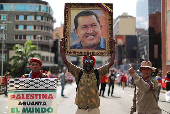 متظاهر يحمل صورة لمادورو وآخر يدعم فلسطين