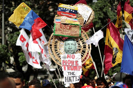 متظاهر يتزين بصور مادورو وعلم فنزويلا