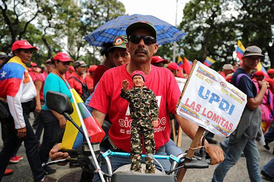 متظاهر يحمل مجسم لمادورو