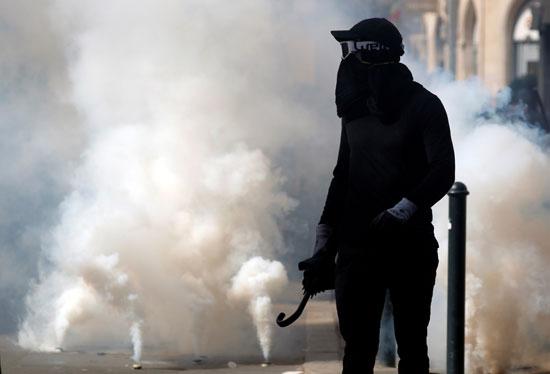 أحد المتظاهرين وسط الدخان