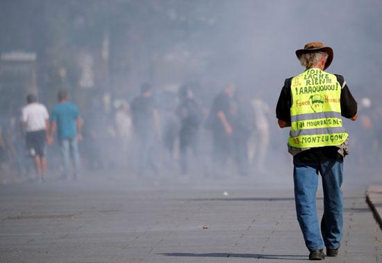 متظاهر يسير وسط الدخان المسيل للدموع