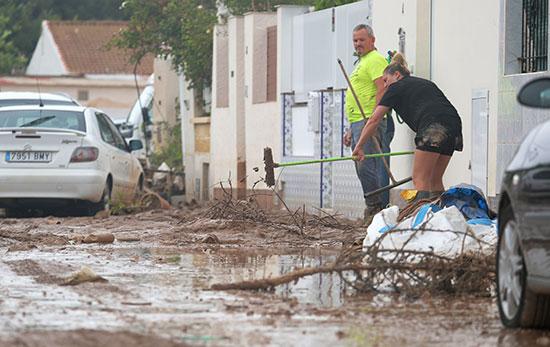 تنظيف لمنزل بجوار الأثاث التالف بعد الفيضانات