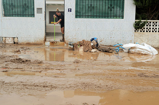 امرأة تنظف مدخلًا للمنزل بعد الفيضان الناجم عن الأمطار الغزيرة في سان خافيير ، أسبانيا