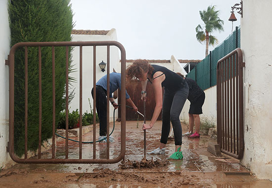 الناس ينظفون مدخلًا للمنزل بعد الفيضانات الناجمة عن الأمطار الغزيرة في سان خافيير