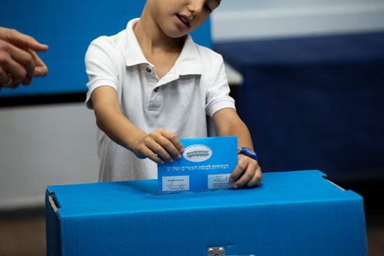 صبي يدلي بصوت والده في صندوق اقتراع أثناء الانتخابات البرلمانية