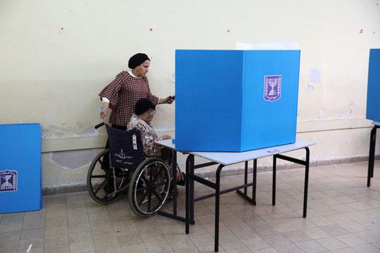 سيدة يهودية متشددة تساعد امرأة أخرى على كرسي متحرك