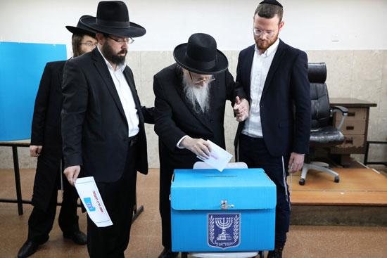 رجال يهوديون متشددون يساعدون رجلاً مسنًا في الإدلاء بصوته
