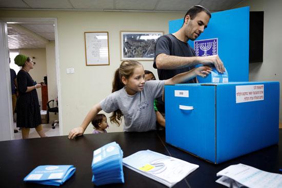 رجل يدلي بصوته مع أحد أقربائه الشباب خلال الانتخابات البرلمانية