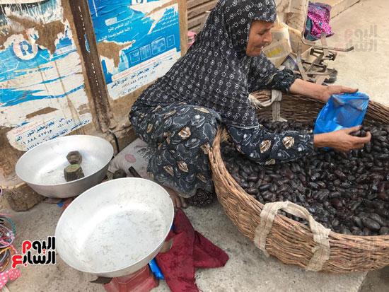 مسنة تعمل في بيع البلح