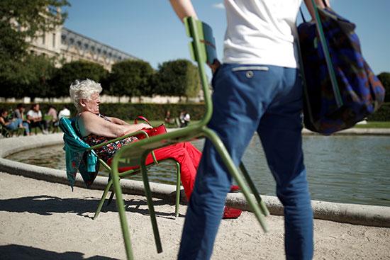 امرأة مسنة تتمتع بالطقس المشمس في حديقة التويلري