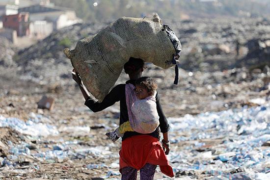 سيدة تحمل طفلها وعلى رأسها جوال من القمامة